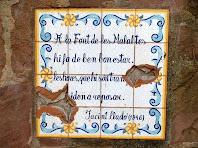 Plafó ceràmic a l'esquerra de la Font de Les Malaltes, amb un fragment d'un poema de Jacint Lladó que li va dedicar el 1946