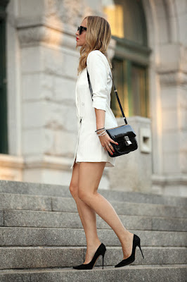 Brooklyn Blonde in an all white shorts suit with black heels and bag