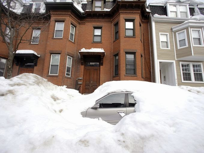 In this Feb. 23, 2015 file photo, a car remains buried in snow along a residential street in South Boston. Boston's miserable winter is now also its snowiest season going back to 1872. The official measurement of 108.6 inches at Logan International Airport Sunday night topped a season record of 107.9 inches set in 1995-96. The final 2.9 inches came in a snowstorm that was relatively tame after a record-setting monthly snowfall of 64.9 inches in February. (Credit: Elise Amendola, AP) Click to Enlarge.
