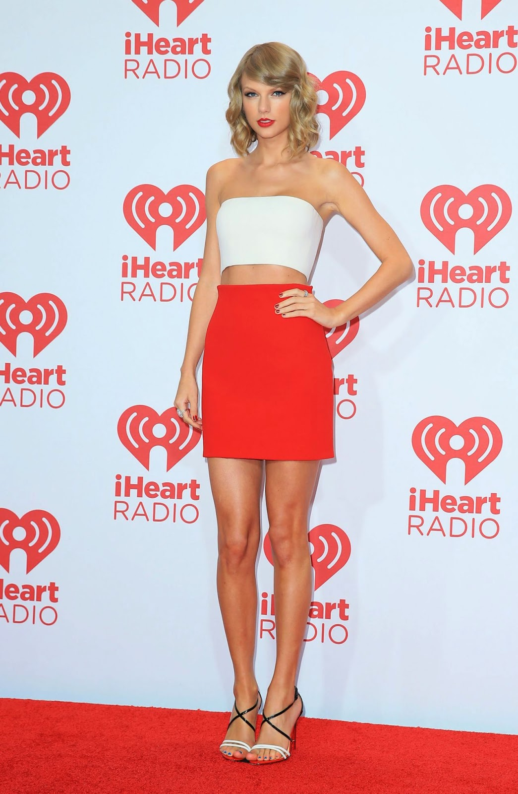 Taylor Swift in a strapless white cropped top and red pencil skirt at the 2014 iHeart Radio Music Festival