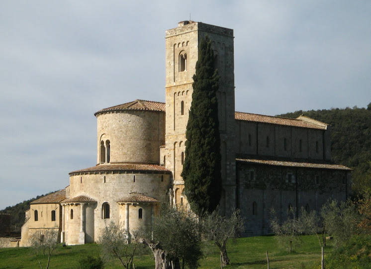 Sant'Antimo abbey with bell tower and cypress tree