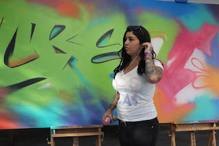 Graffiti Artist Amy working on her colorful canvas with greens, purples, pinks and turquoise. .