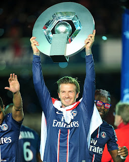 Celebration: Beckham lifts the Ligue 1 trophy with an England flag draped around his neck