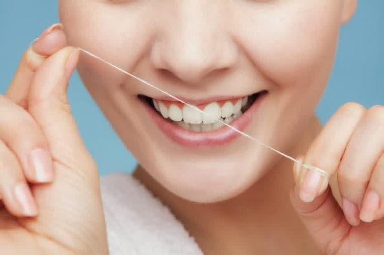 tips dan cara menjaga gigi tidak berlubang - pakai benang gigi