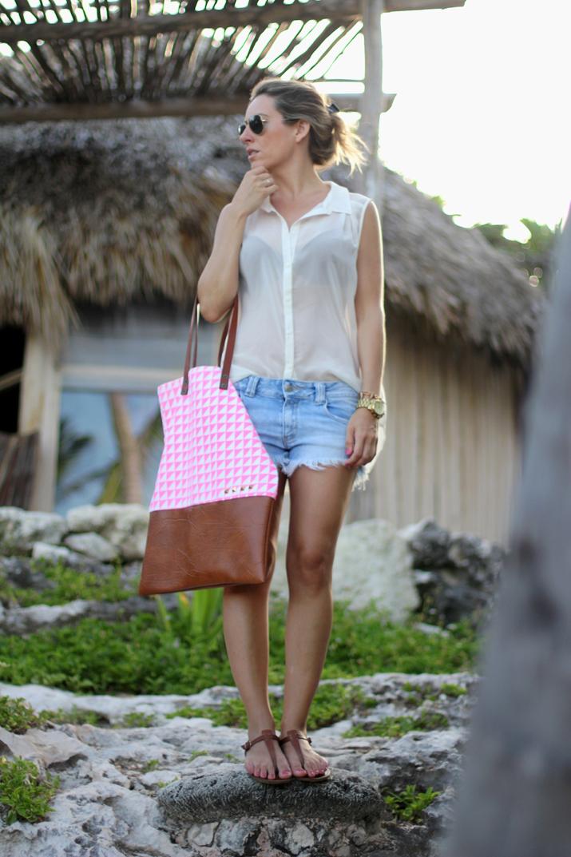 Bloguera con outfit de verano en el Caribe. Look con shorts, camisa sin mangas transparente, bolso de tela con tachuelas y sandalias planas.