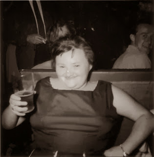 My mum in her twenties holding up a pint of beer.