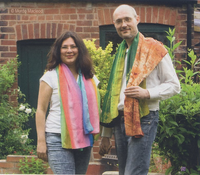 The two directors of LitB are standing in a garden.  Both are wearing colourful scarves