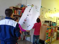 Entre varios alumnos van subiendo el papel continuo a la pared para colgarlo