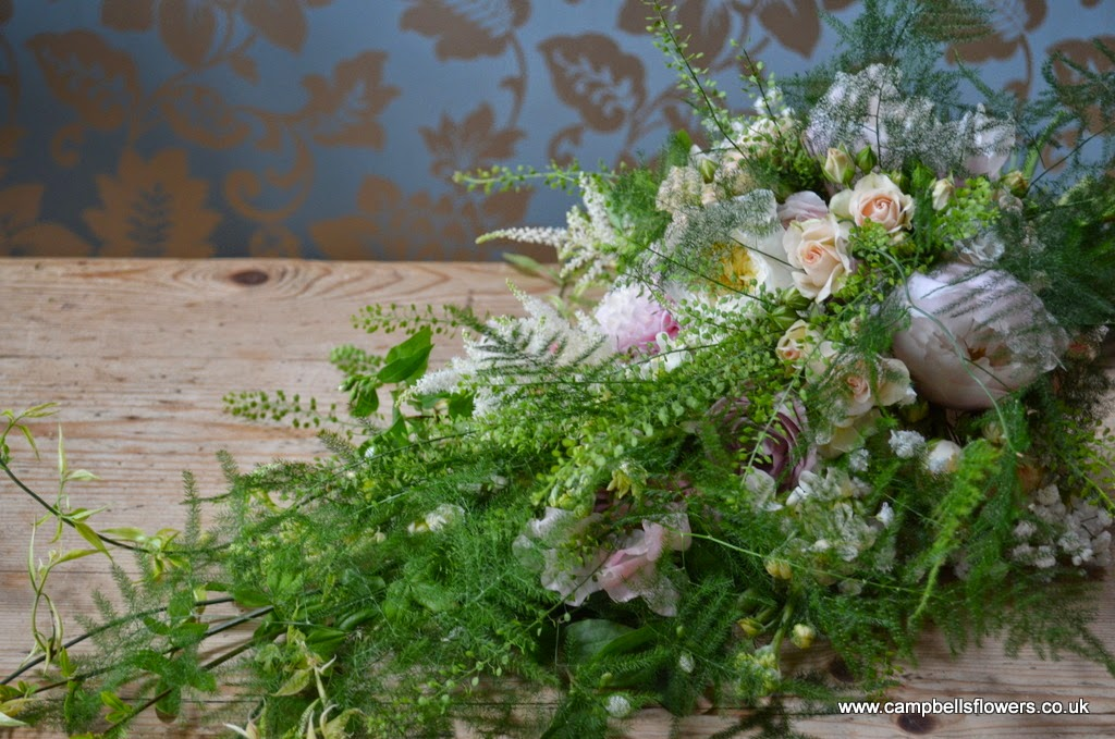 An oversized, just picked wild flower bouquet in a cascading style.