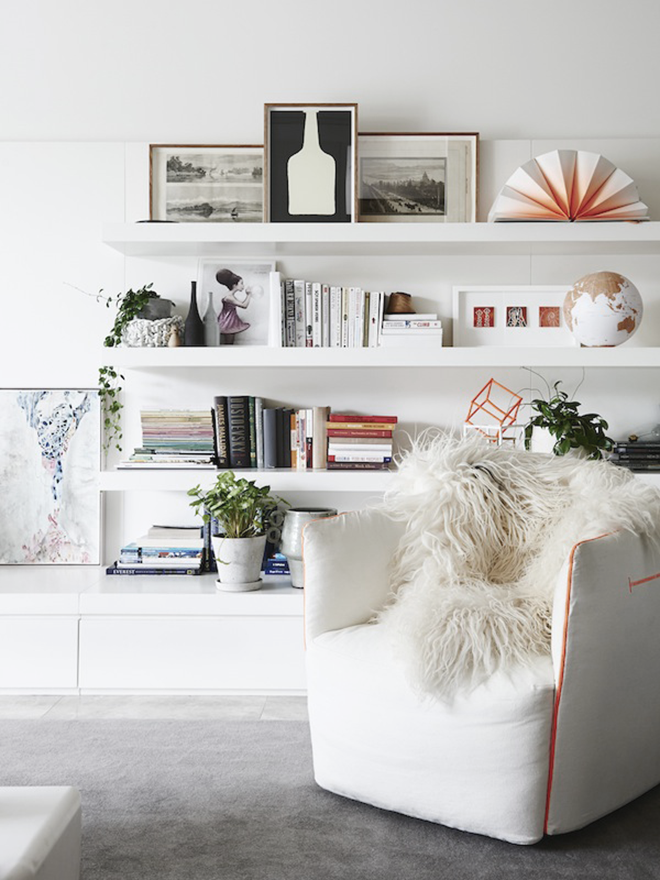 White living room with floating shelves
