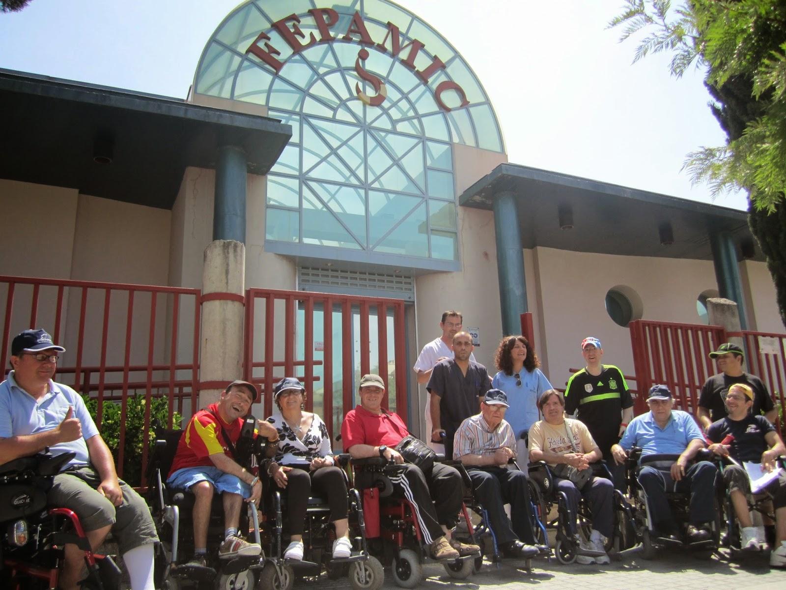 Trece personas posan ante la puerta de la Unidad de Día de FEPAMIC.
