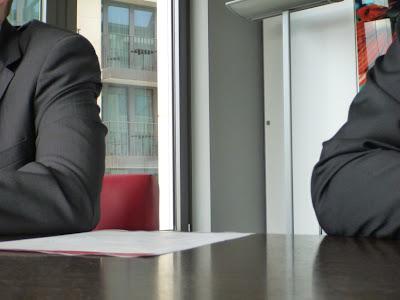 Graue Zweireiher (Schulter-/Armpartien) vor moderner Bürowand. Die Herren sitzen am Tisch ...