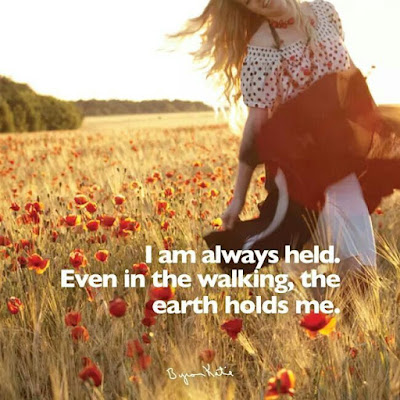 """I am always held. Even in the walking, the earth holds me."" ~ Byron Katie; Picture of a woman walking in a field of red flowers."
