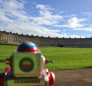 A toy robot looking at the Royal Crescent, Bath