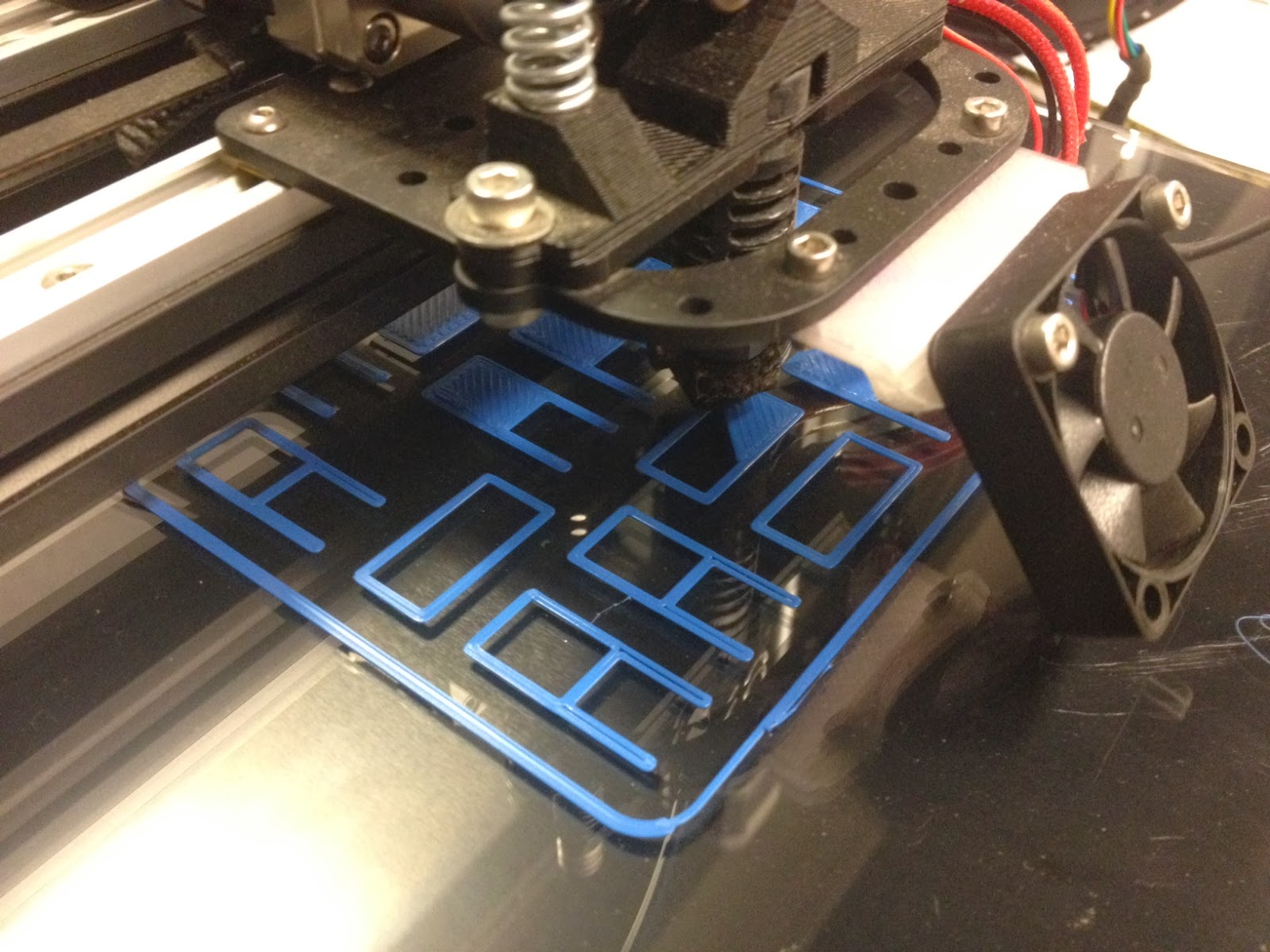 3D printer beginning to print blue plastic miniature chair models.