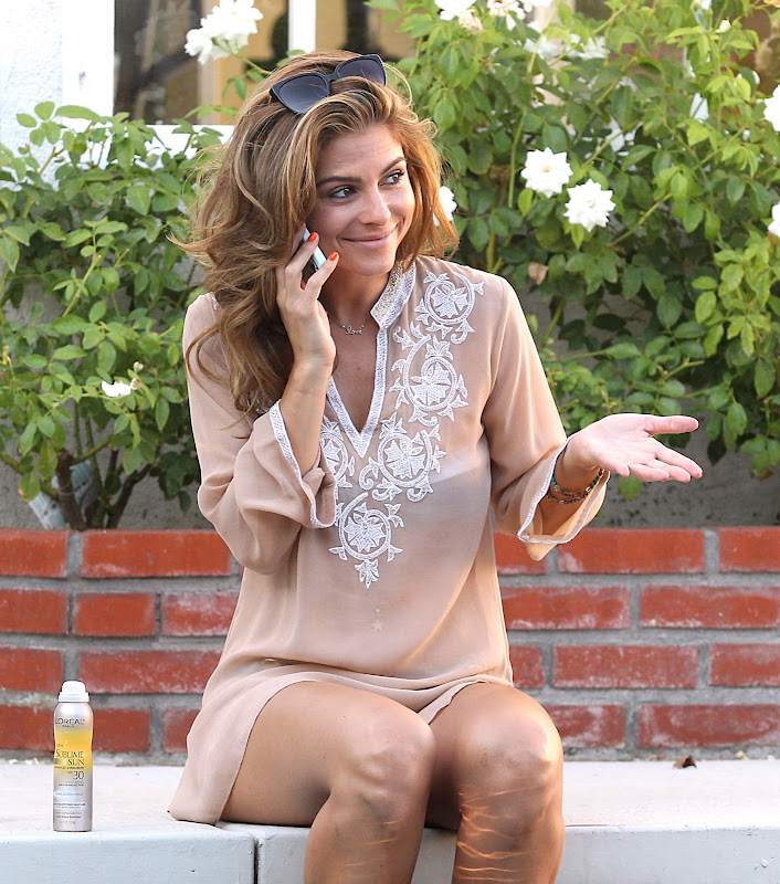 Maria Menounos talking on the phone by the pool at her home