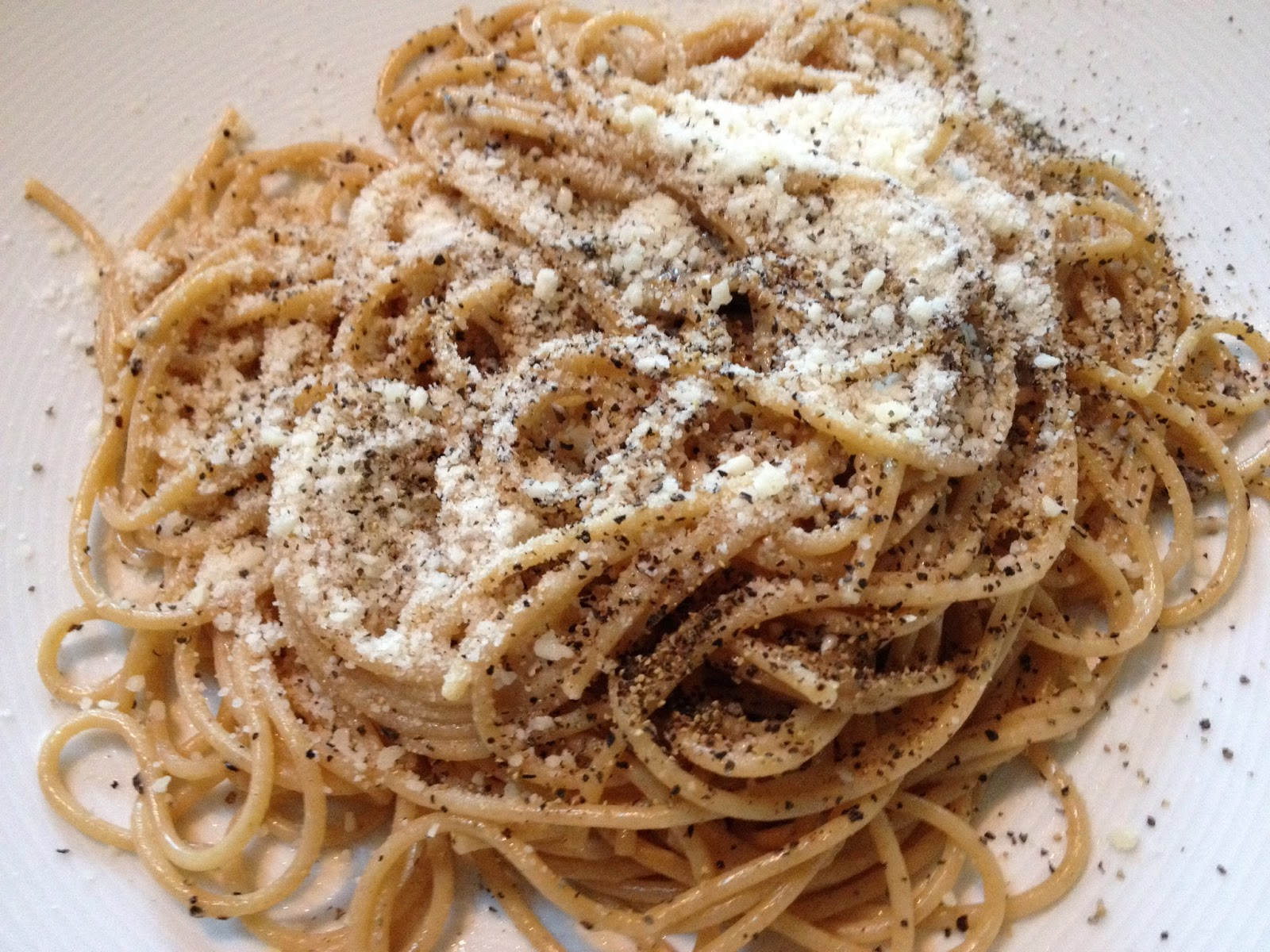 Organic whole-wheat spaghetti with grated cheese and black pepper.