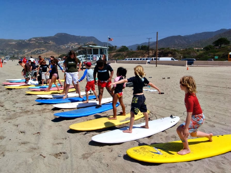 Aloha Beach Camp kids with surfboards learning to surf on the sand at Zuma Beach