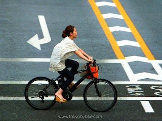 Woman cycles in bicycle lane in Tokyo, Japan