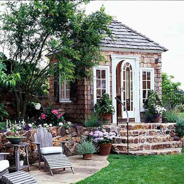 caseta revestida de madera en el jardin con techo a cuatro aguas