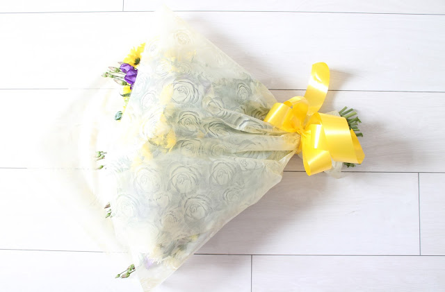 bouquet of yellow white and purple flowers on white wooden floor with yellow bow