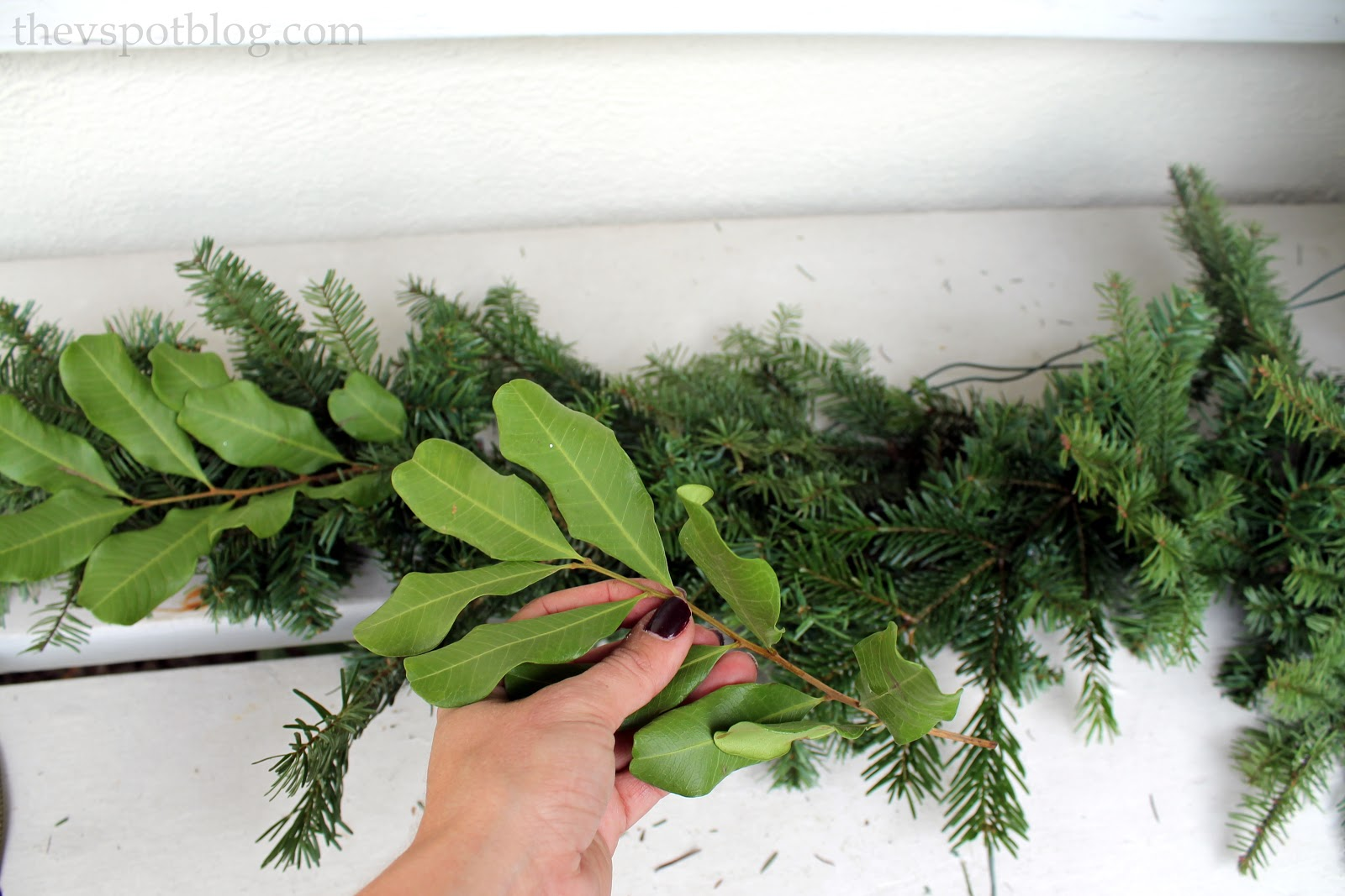 sprucing up a fake garland with real greenery - Fresh Christmas Greenery