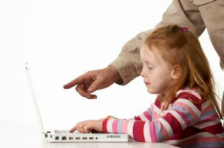 Image of a child at the computer with an instructor's hand