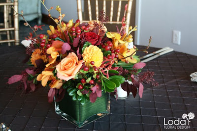 Fall wedding centerpiece, orange and maroon centerpiece, orange mokara orchids, red hypericum berries, orange roses
