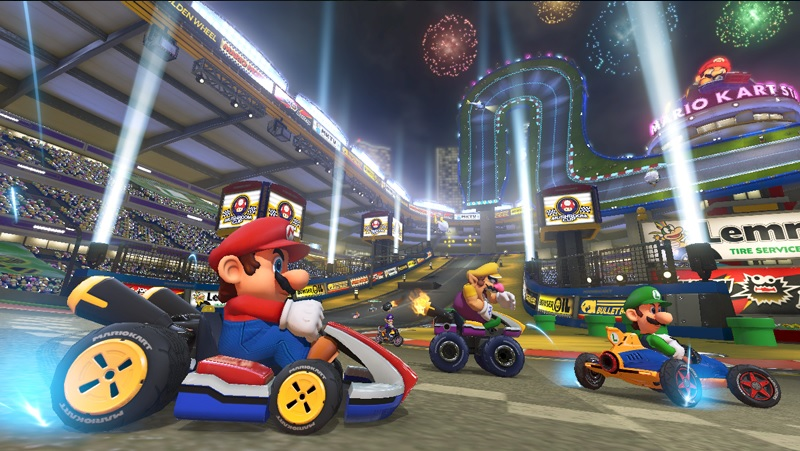 Screenshot of Mario Kart 8 with title character driving his kart in large stadium. Wario and Yoshi can be seen in the background, along with many others in the distance.