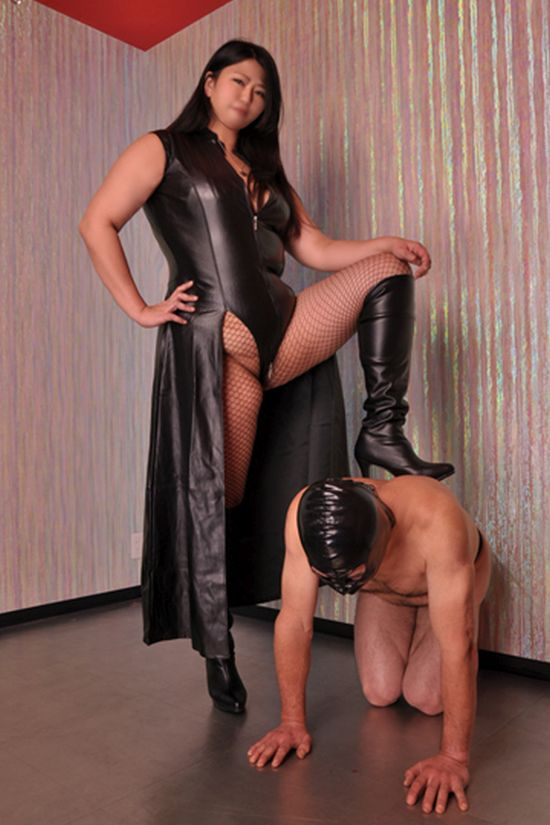 japanese dominatrix with curves in leather dress, her boot firmly placed on her slave's back
