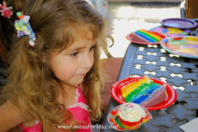 kid eating rainbow cake