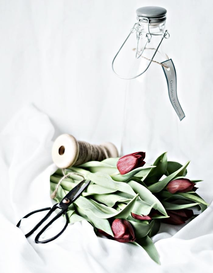 rote Tulpen auf einem weißen Tuch, an einer Glasflasche dekoriert