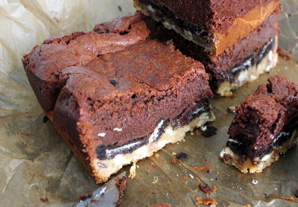 Slutty Brownies Made From Brownie and Chocolate Chip Cookie Layers Sandwiching An Oreo Cookie