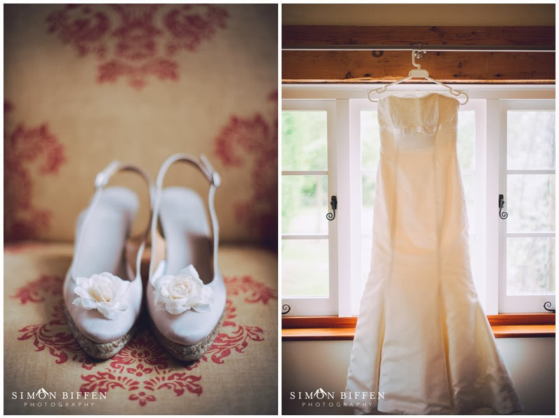 Bridal shoes and wedding dress hanging up