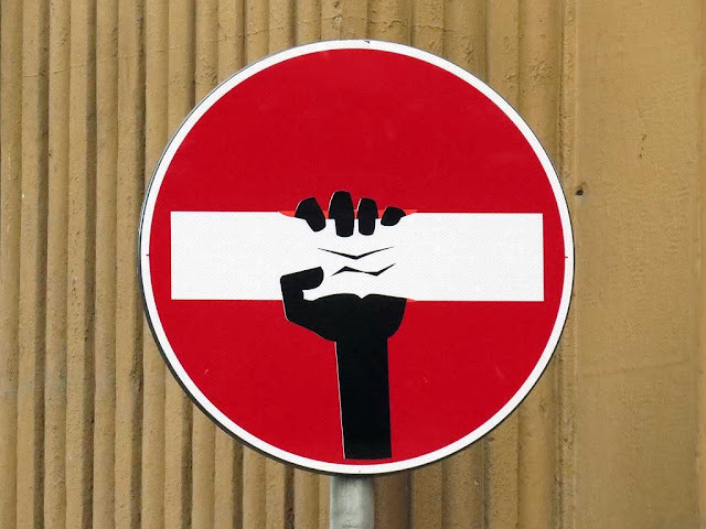 Squeezing the bar on a no-entry sign, Clet Abraham, Florence