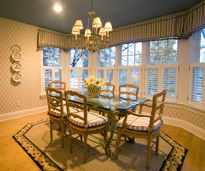 traditional dining surrounded mostly by windows and centered to a classic chandelier