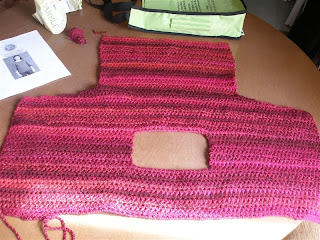 reddish pink sweater in progress laid flat on a table along with a bit of yarn, the pattern, and a green yarn bag