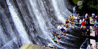 Para Pengunjung Biasanya Duduk Dan Berbaring Di Bawah Air Terjun Image