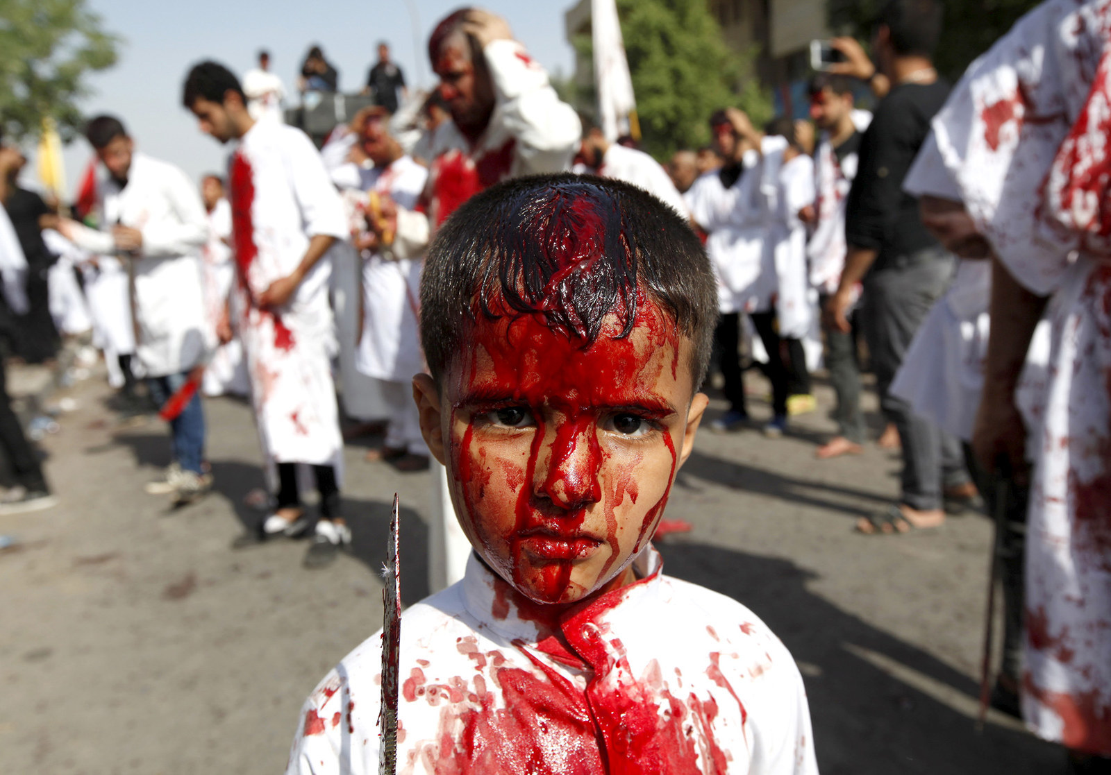70 Of The Most Touching Photos Taken In 2015 - Iraq Shi'ite Muslims tap themselves with knives and razors to celebrate Ashura in Baghdad. The festival commemorates the death of Imam Hussein, grandson of Muhammad.