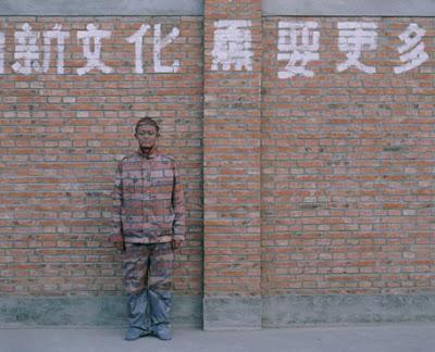 Liu Bolin en un muro de ladrillos