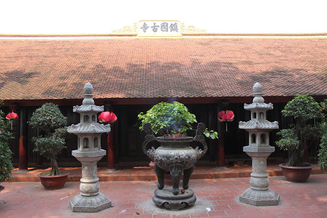 Buddhist temple with burning incense and worship statues is situated behind the oldest pagoda at Tran Quoc Pagoda in Hanoi, Vietnam