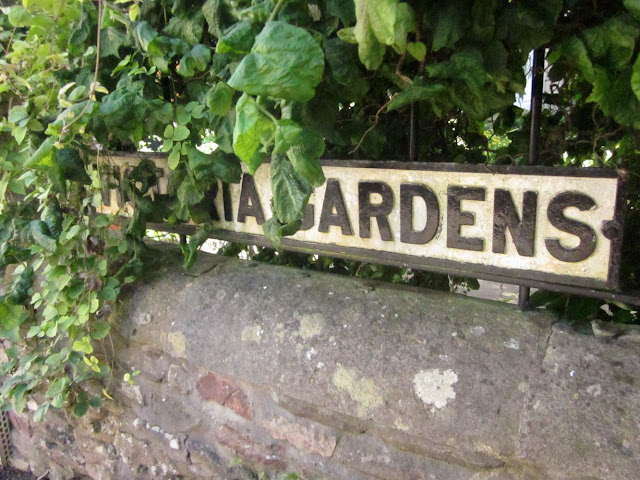 """Victoria Gardens"" roadsign partially concealed by hazel tree"