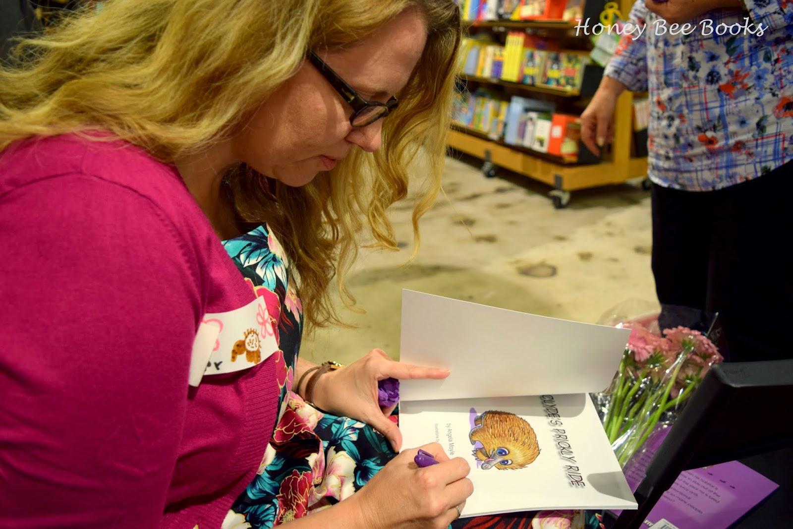 Canberra Author Angela Moyle signing a copy of Clyde's Prickly Ride