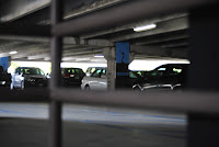 photo of cars parked in a parking structure seen through rails