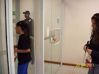 Natielle passando na porta giratória e Gi aguardando sua vez