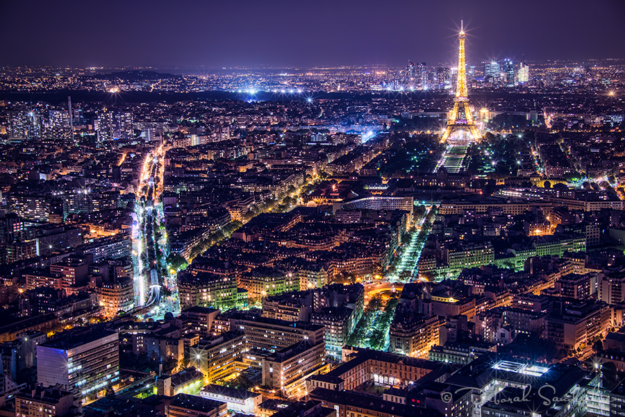Paris at night with tower in golden lights surrounded by lights in the city.
