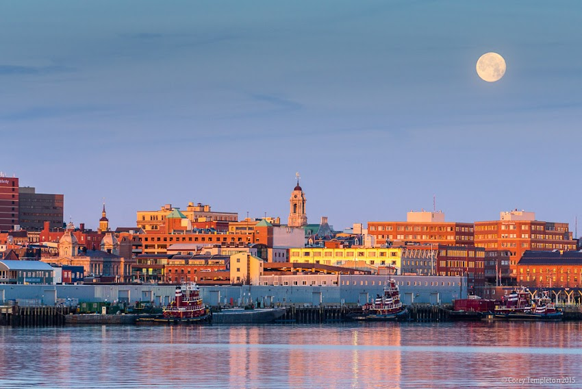 Portland, Maine USA December 2015 photo by Corey Templeton. An almost-full moon setting behind the Portland skyline this morning. Viewed from Bug Light Park in South Portland.