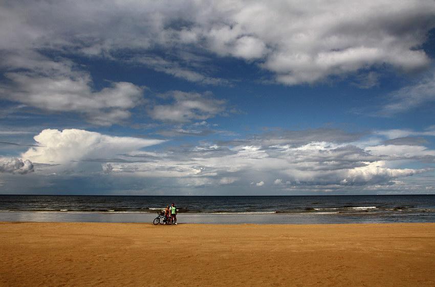 Foto sobre a praia. Ao centro um casal com duas bicicletas numa pausa entre a viagem ao longo do areal, bem junto ao mar calmo