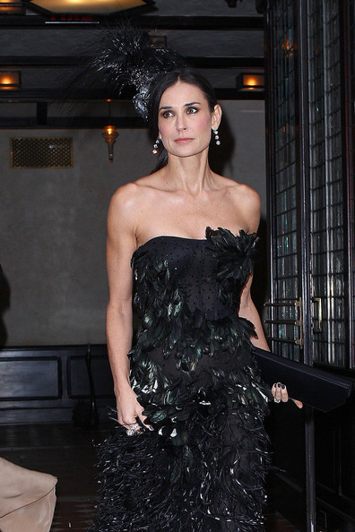 Demi Moore in a dramatic black, feathered strapless Prabal Gurung gown and a matching feathered Philip Treacy headpiece at the 2011 MET Gala.