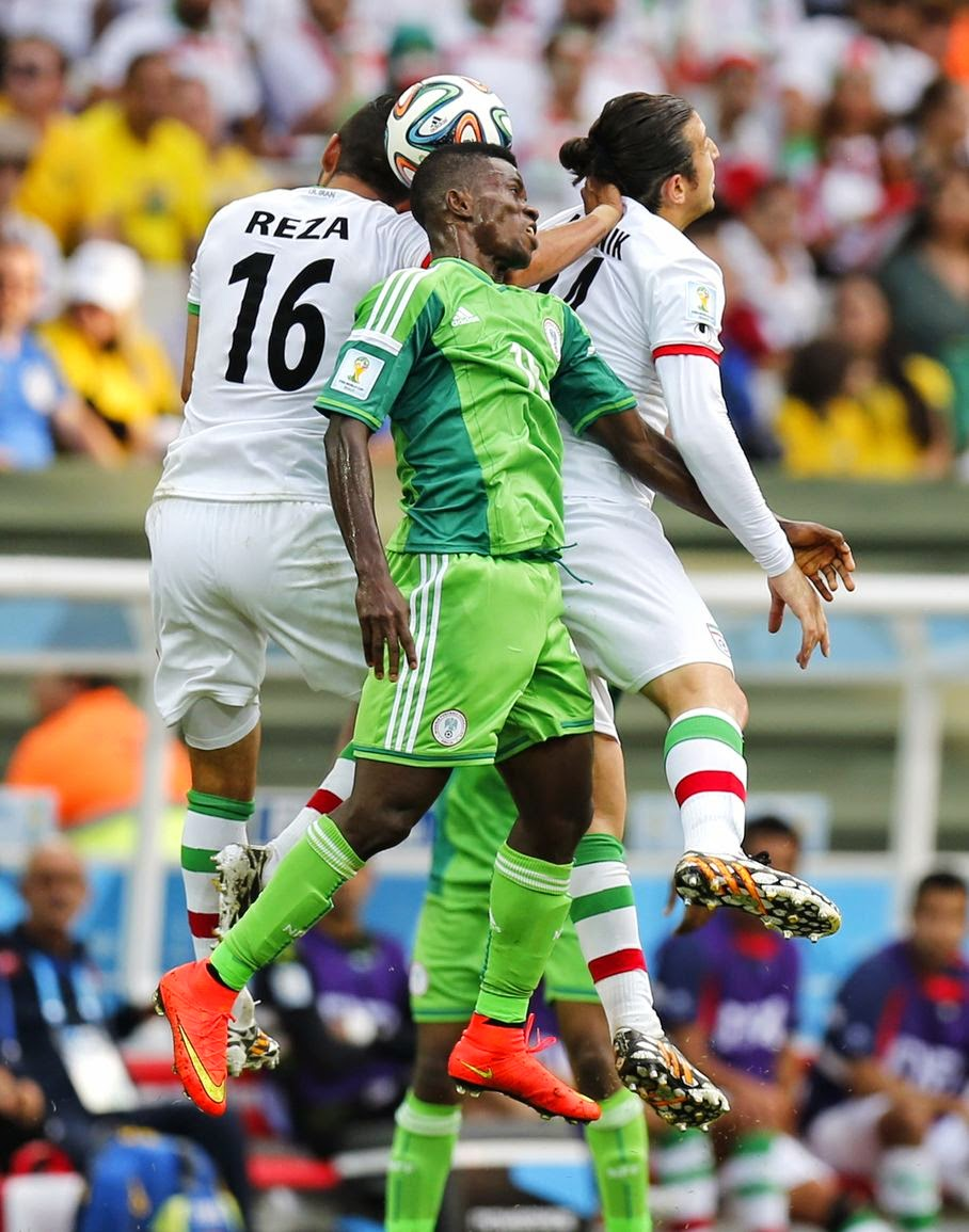 Nigeria's Ramon Azeez goes up against Iran's Reza Ghoochannejhad (16) and Andranik Teymourian during the group F World Cup soccer match between Iran and Nigeria at the Arena da Baixada in Curitiba, Brazil, Monday, June 16, 2014.